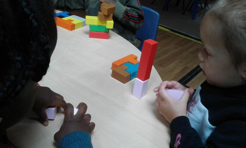 Uses blocks to create their own simple structures and arrangements.