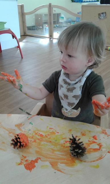 Enjoys the sensory experience of making marks in damp sand, paste or paint.