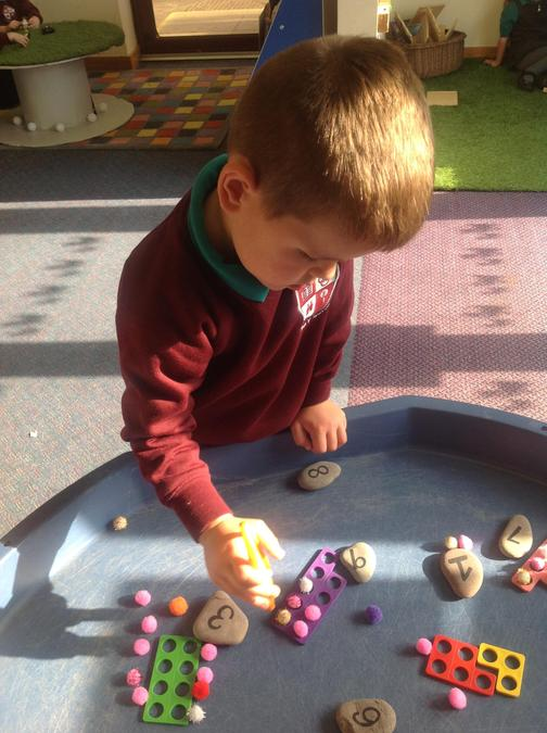 Matching the correct number of pom-poms to the numicon and numeral pebbles.