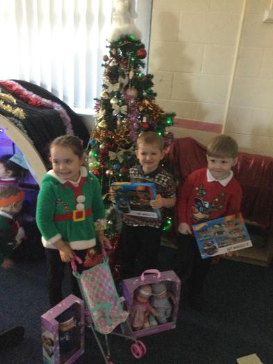 EYFS children receiving their gifts from the PTA