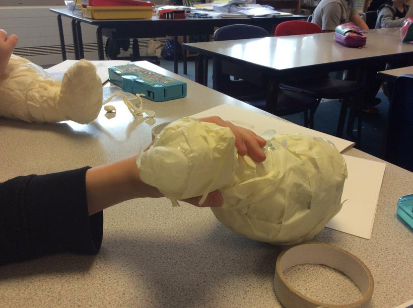 Using masking tape to sculpt ears and nose