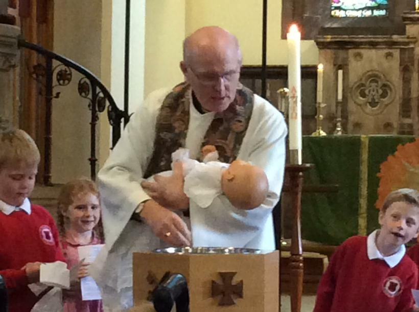 Father Peter poured water on the baby's head.