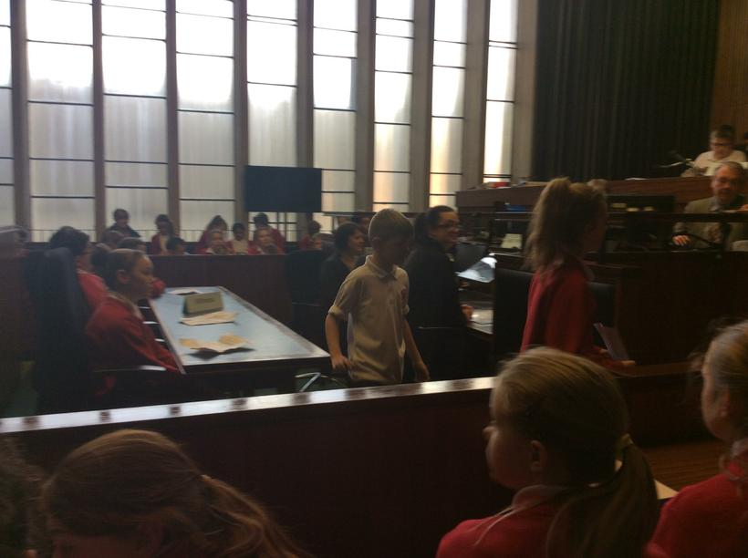 Court Usher taking a witness to the stand.