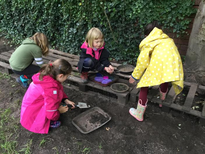 In the mud kitchen creating potions.