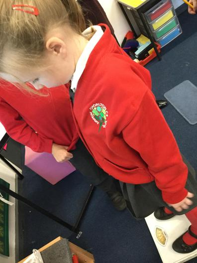 Using the bathroom scales to see how much we weigh