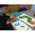 Child cuts out painted paper to create his picture