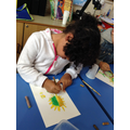 Child uses pastels to draw a sunflower.