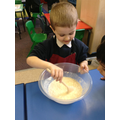 Child mixes ingredients for a pancake.