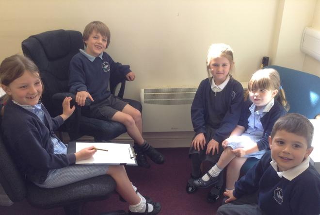 A group of children sitting on chairs