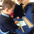 A child uses a ruler to measure width.