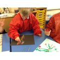 Child uses paint to create a blossom painting.