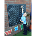 Child finding numbers in a 100 square.