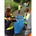 Child uses litter picker and picks up litter.