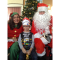A child has their photo with Santa & the Head Elf.