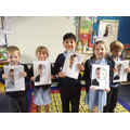 Children showing their portraits to the class.