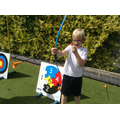 Child positions his arrow in his bow for archery.
