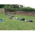 Class 1 make a wriggly worm with their bodies.