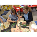 Children use paint to make blossom paintings.