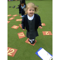 Child finding numbers and jumping on them.