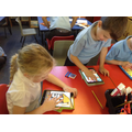 Children use an ipad to draw a burning Tudor house