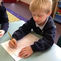Yr R child practises writing his name.