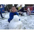 A child makes a snowman.