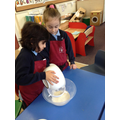 Children mix ingredients for a pancake.