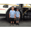 Class 2 children stand by lorry wheel.