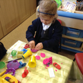 Child in the creative corner using play doh.