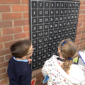 Children finds numbers on a 100 square.