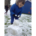 A child builds a snowman