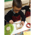 Child using round cutter to make the head shape.