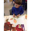 A child uses watercolours to paint a leaf.