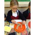 Child spreads butter on her open sandwich.