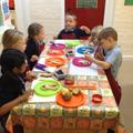Group of children making an open sandwich.