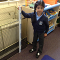 Child uses a ruler to measure the heater height.