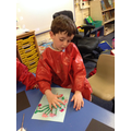 Child paints blossom using his fingers