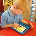 Child uses an ipad to draw a burning Tudor house