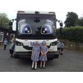 Children stand ar the front of much the huge lorry