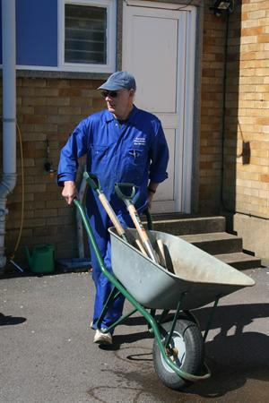 Mr Brigham uses a wheelbarrow to carry his tools