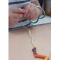 Threading pasta or beads onto sting.