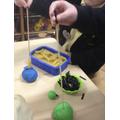 Pushing spaghetti into playdoh/plasticine/blue tack.