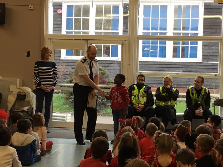 Year 4 pupil receiving his certificate for bravery