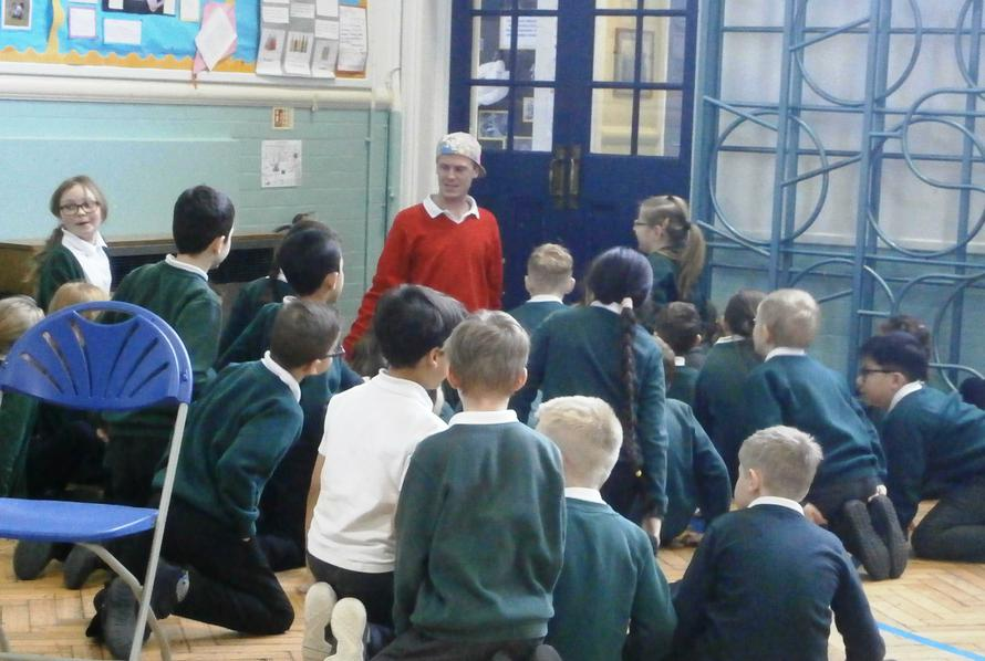 Year 3 and 4 children talk  to one of the actors
