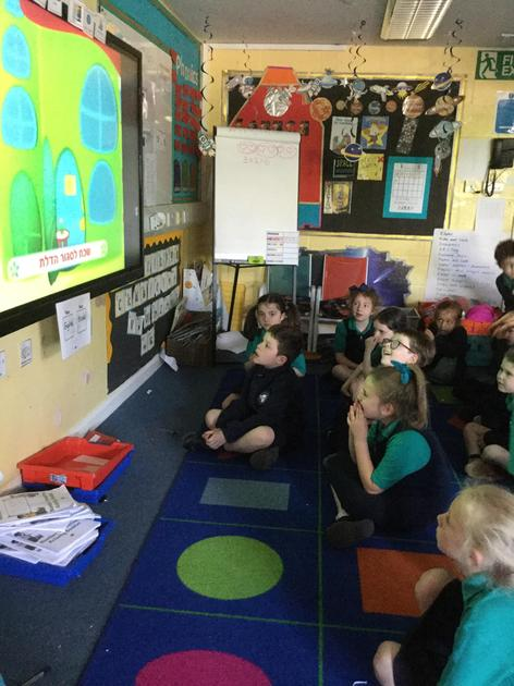 Year 1 sitting on carpet spaces, watching a children's song in Hebrew.