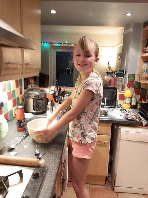 Evie busy in the kitchen baking her pizza.