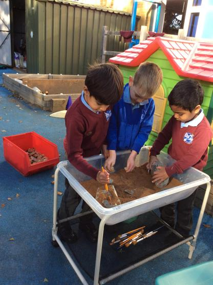 Brushing the earth away to excavate the fossils.
