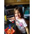 Ellyn is using an apple to make pumpkin prints
