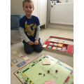Oliver being the banker in monopoly for his maths!