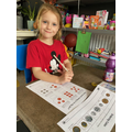 Mia working hard with recognising coin values